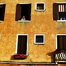 Bored man over the windows in old building Venice. by georgelim