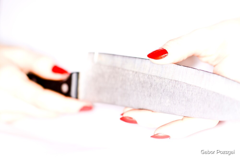 High-key female hand trying the sharpness of knife by Gabor Pozsgai