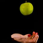 Female hand throwing a green apple by Gabor Pozsgai