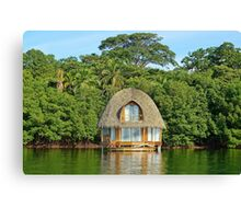 Tropical bungalow over water with thatched roof Canvas Print