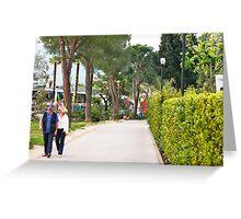 a couple walking alone the side of lake garda Greeting Card