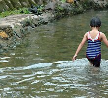 girl playing in the water by bayu harsa
