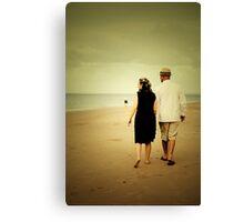 Couple walking down the beach Canvas Print