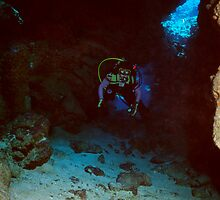Diver exploring a sun-lit cave in Caribbean by outcast1