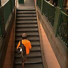 Man In Orange Climbing Stairs by Andrew  Makowiecki