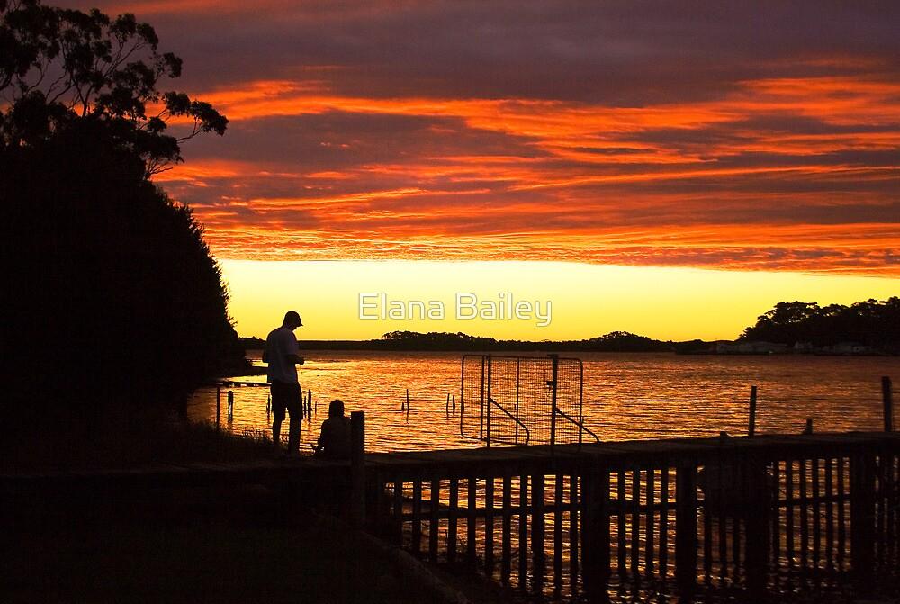 A couple watch the sunset at Strahan, Tasmania by Elana Bailey