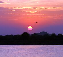 A colourful sunset over a lake. by debjyotinayak
