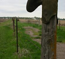 Old worn out cowboy boot on a wooden fence post by PhotoCrazy6