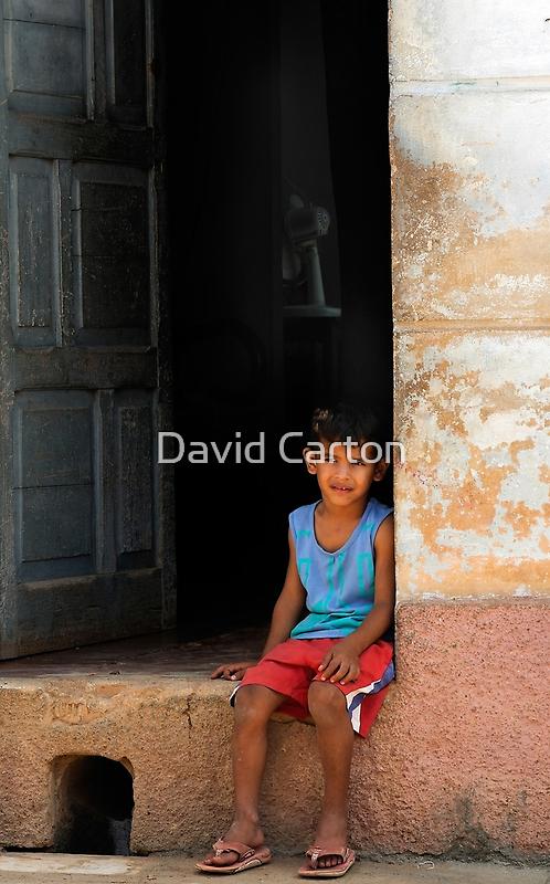 Cuban boy sitting on door step, Trinidad, Cuba by buttonpresser