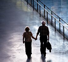 Hand in hand, couple walking together by John Englezos