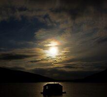 Backlit small hut on sea by Gabor Pozsgai
