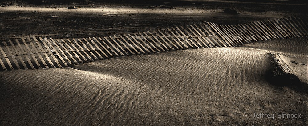 Sand and fence by Jeffrey  Sinnock