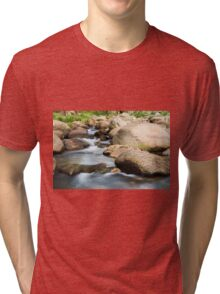 Rocks covered in moss in a creek bed. Tri-blend T-Shirt
