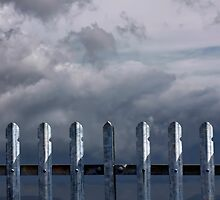 Metal fence with stormy dark clouds by steveball