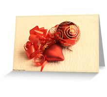 Red Christmas ball with red satin glass heart with red ribbon on white damask linen Greeting Card