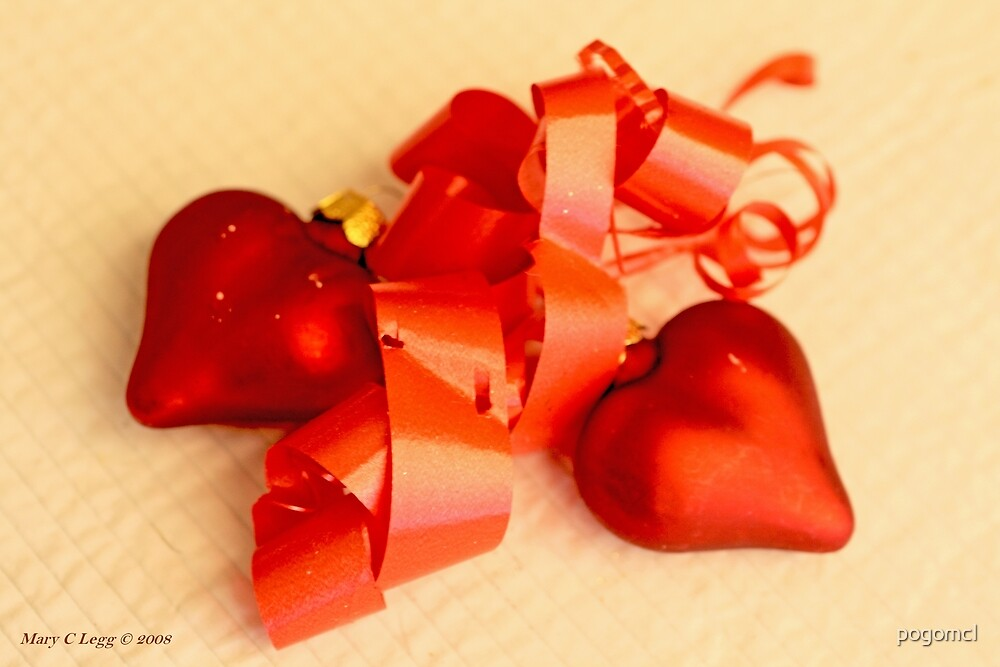 Two red satin glass hearts with red ribbon on a white cotton mat by pogomcl
