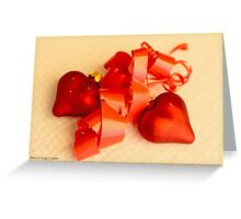 Two red satin glass hearts with red ribbon on a white cotton mat Greeting Card