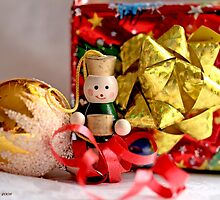 Toy soldier with an accordian  stands before a gaily wrapped  Christmas package in red foil by pogomcl