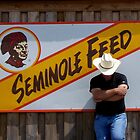 Cowboy Endorsed - A Cowboy relaxing against a Seminole Indian Billboard by Rick Short