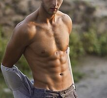 attractive athletic man with a naked torso takes off his shirt by Tverdokhlib