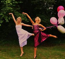 Pretty blonde bride and bridesmaid with balloons dance ballet-style by imageunlimited
