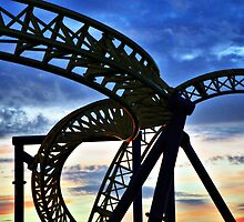 Coaster - Twisting frame of a roller coaster taken against a pastel sunrise by Lord William Chard