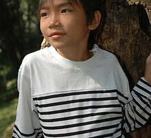 little boy stand up beside the tree by bayu harsa