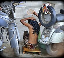 Girl, washing in the streets of Delhi, India by Catherine Ames