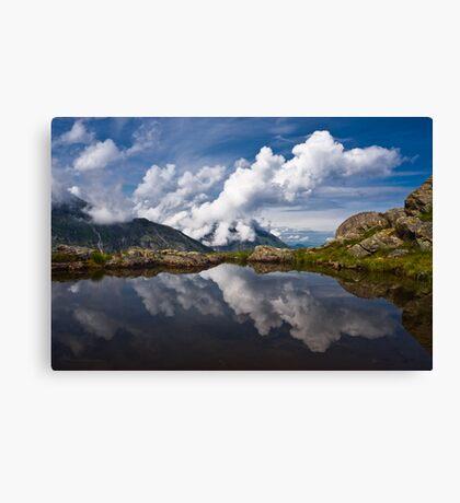 Trolls' clouds reflecting in Norwegian mountain lake. Canvas Print