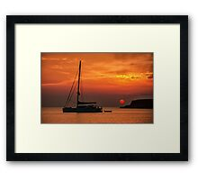 Silhouette of a sailing boat at sunset Framed Print