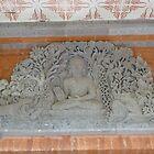 Buddha stone carving above door. by Amanda Gazidis