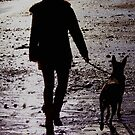 Girl walking dog on beach by Mark Cassidy