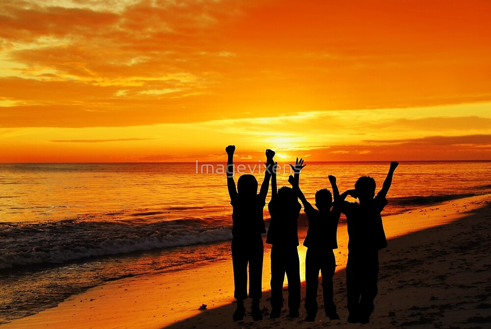 Children silhouettes on a  sunset beach by Imagevixens