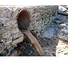 Dirty water flows from a brown rusty sewer pipes Photographic Print