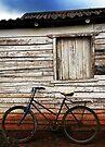 Bike leaning against farm building, Vinales, Cuba by David Carton