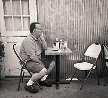 New York City: man alone at restaurant table by Ron Greer