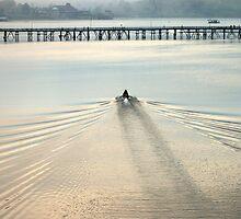 Boat approaching man-made wooden bridge by juat