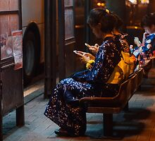 Japanese girls in yukata glued to smartphones by Philip Seifi