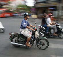 Life rolls by in Ho Chi Minh by Chris Cherry