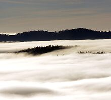 Distant hills through the clouds below us by Ron Co