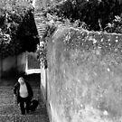 woman climbing hillside street in Portugal by Stephen Frost