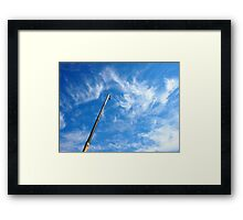 The boom of the crane on a diagonal against a blue sky Framed Print