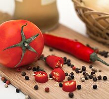 Tomato and paprika on a cutting board by Sviatlana Kandybovich