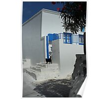 black cat at front of a white house in santorini Poster