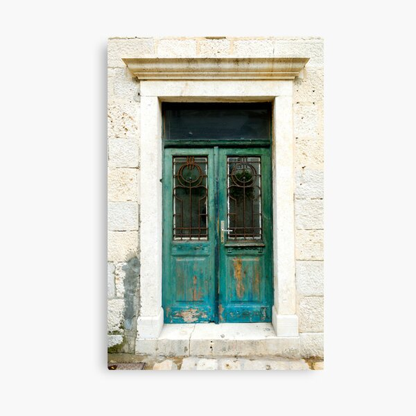 Old green door with antique art-nouveau wrought iron. Canvas Print