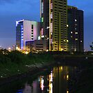 The Kuningan Place (by night) by buildings