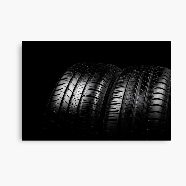 Close up view of a car tyres isolated on a black background Canvas Print