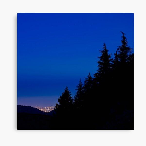 Le luci della città oltre il bosco Canvas Print