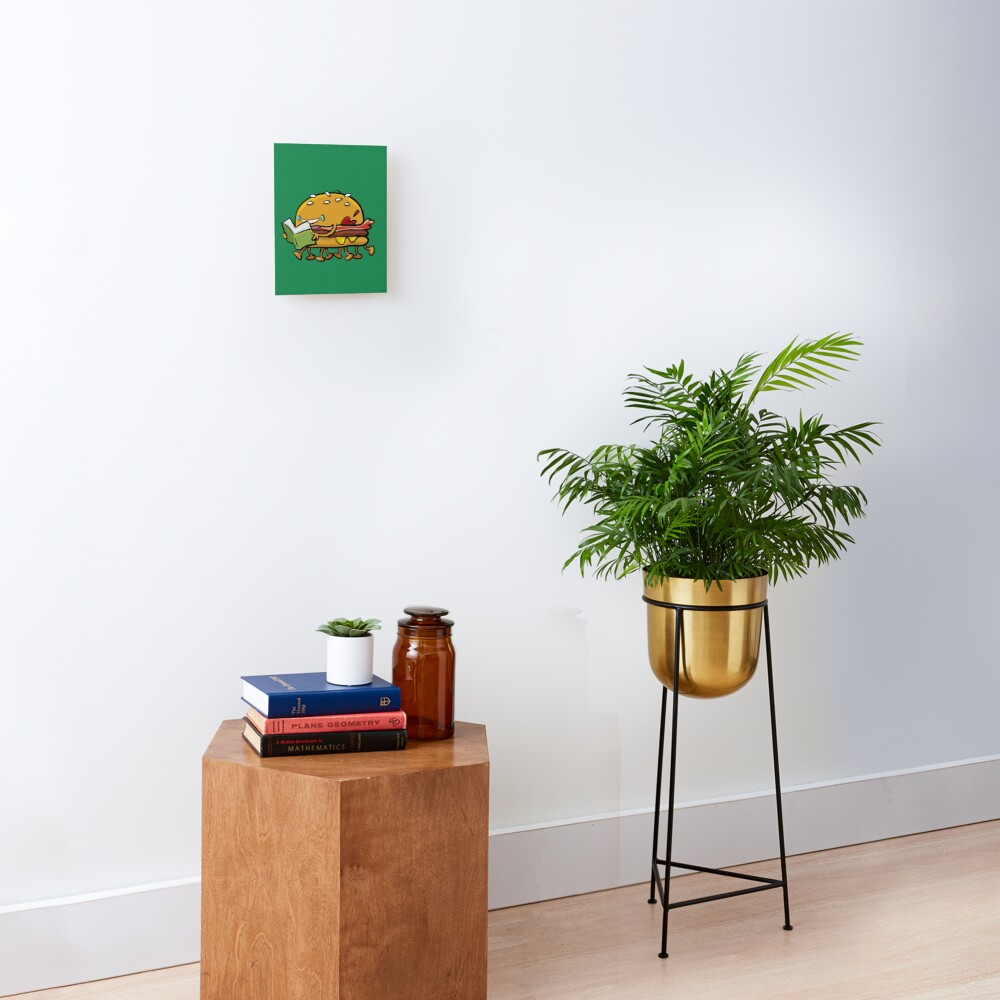 burger with legs reading a book Mounted Print
