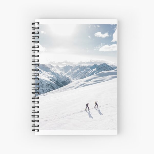 2 hikers in the snow on a mountain. Spiral Notebook